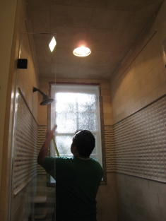 Putting on the finishing touches of tiles to the Hall shower