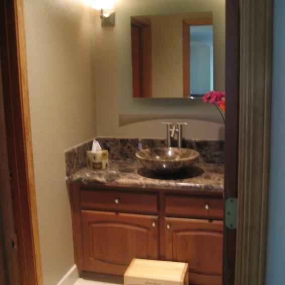 Powder room with Emperador dark marble vessle and counter top