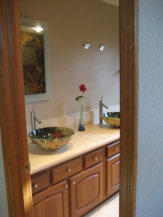 Hall bath with Crema Marfil Countertop with glass vessel sinks